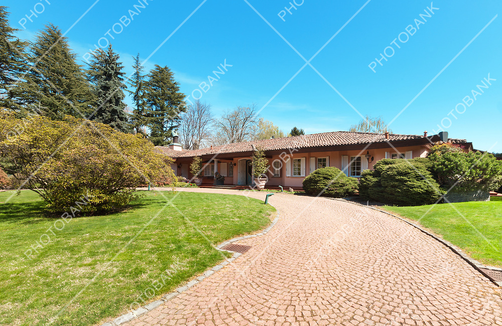 Green garden and beautiful house in a sunny spring day