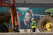 An excavator and aspirational poster on wall during building of 2012 Olympic Westfield City shopping centre, Stratford. A glamorous woman representing the good times - wealth and beauty and the symbols of affluence - while the working Man is seen small in comparison, the downtrodden Man. The £1.45bn complex houses more than 300 shops, 70 restaurants, a 14-screen cinema, three hotels, a bowling alley and the UK's largest casino. It will provide the main access to the Olympic park for the 2012 Games and a central 'street' will give 75% of Olympic visitors access to the main stadium so retail space and so far 95% of the centre has been let. It is claimed that up to 8,500 permanent jobs will be created by the retail sector..