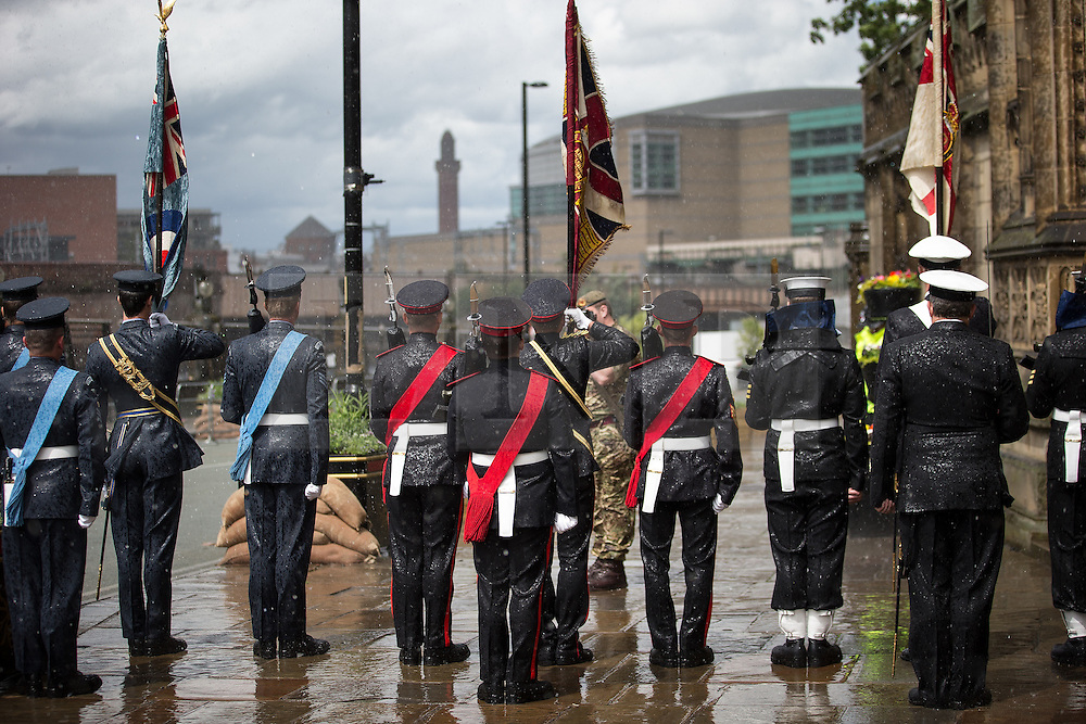 © Licensed to London News Pictures . 01/07/2016 . Manchester , UK . Heavy rain and hail drenches people outside Manchester Cathedral . Somme100 events in Manchester City Centre to commemorate the 100th anniversary of the first day of the Battle of the Somme . Photo credit : Joel Goodman/LNP