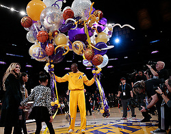 File photo of The Los Angeles Lakers' Kobe Bryant is gifted a passel of balloons as his daughter Gianna, right, wife Vanessa and other daughter Natalia join him for a ceremony celebrating his passing of Michael Jordan as the third-leading scorer in NBA history before a game against the Oklahoma City Thunder at Staples Center in Los Angeles on Friday, Dec. 19, 2014. (Robert Gauthier/Los Angeles Times/TNS/ABACAPRESS.COM)