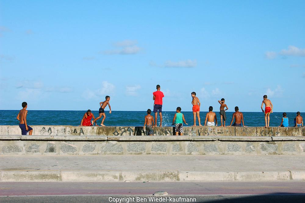 Group of children playing on the coastal wall on Brasilia Teimosa beach in Recife Brazil