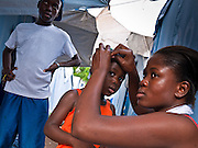 16 NOVEMBER 2010 - PORT-AU-PRINCE: HAITI: A woman does her daughter's hair in a tent city in a park in the Delmas neighborhood of Port-au-Prince. The Jan. 12 earthquake has left hundreds of thousands of Haitians homeless and 10 months after the earthquake Haitians are still living in tents donated by foreign governments and NGOs. PHOTO BY JACK KURTZ