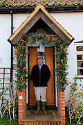 Elderly man standing in his porch having decorated it for Christmas, Suffolk, England, UK