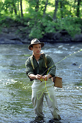 man fly fishing in a river