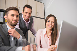 Three young business partners meeting in office