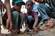 Youngsters play marbles.  The slum of Cheetah Camp on the outskirts of Mumbai, India is a predominantly muslim community on living on the fringe while the city continues to grow.