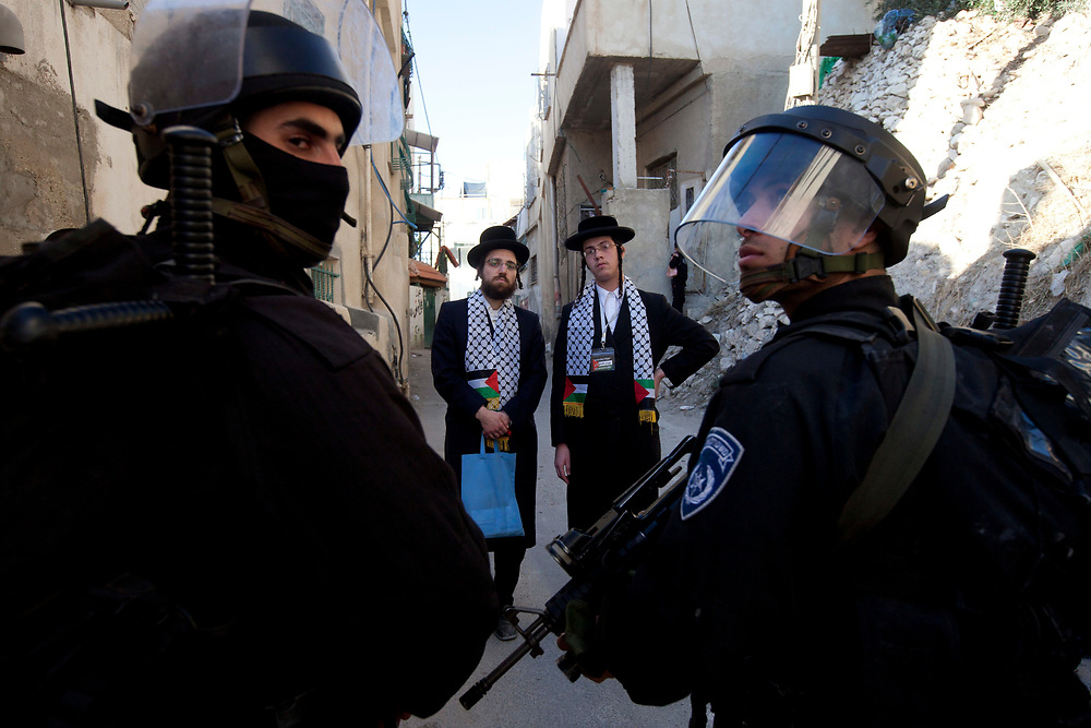 Israeli policemen block members of Neturei Karta, a fringe ultra-Orthodox movement within the anti-Zionist bloc at the entrance to Beit Yonatan in the east Jerusalem neighborhood of Silwan, prior to a visit by Israeli parliament members of the National Union party to the building that houses several Jewish families in the mostly Palestinian area on December 27, 2010.