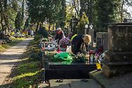 Ladies make graves neatly at Rakowicki cemetery in Krakow, Poland 2019.