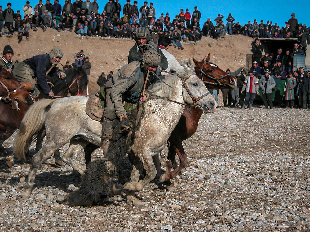 Image of a Tajik horseman charging off with the buz (a stuffed goat) out of melee toward the finish at a buzkashi event in the village of Kostarosh, northwest Tajikistan