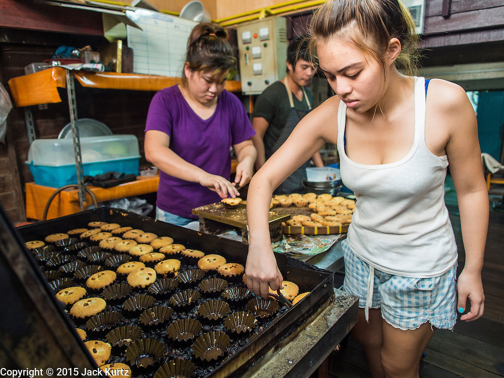 """06 FEBRUARY 2015 - BANGKOK, THAILAND: Workers at Thanusingha Bakery pull traditional Thai Catholic desert cakes out of the baking pans. The cakes are called """"Kanom Farang Kudeejeen"""" or """"Chinese Monk Candy."""" The tradition of baking the cakes, about the size of a cupcake or muffin, started in Siam (now Thailand) in the 17th century AD when Portuguese Catholic priests accompanied Portuguese soldiers who assisted the Siamese in their wars with Burma. Several hundred Siamese (Thai) Buddhists converted to Catholicism and started baking the cakes. When the Siamese Empire in Ayutthaya was sacked by the Burmese the Portuguese and Thai Catholics fled to Thonburi, in what is now Bangkok. The Portuguese established a Catholic church near the new Siamese capital. Now just three families bake the cakes, using a recipe that is 400 years old and contains eggs, wheat flour, sugar, water and raisins. The same family has been baking the cakes at the Thanusingha Bakery, near Santa Cruz Church, for more than five generations. There are still a large number of Thai Catholics living in the neighborhood around the church.        PHOTO BY JACK KURTZ"""