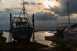 A fishing boat is in silhouette against the sunlit water in the early evening at West Mersea, Mersea Island, near Colchester in Essex. West Mersea, Essex, July 11 2019.