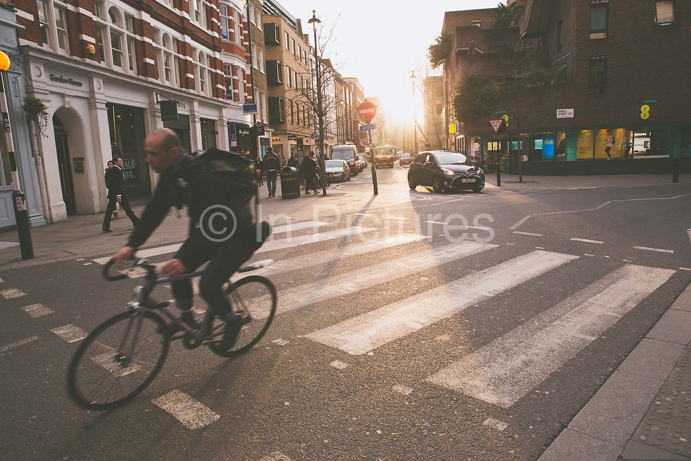 A male cyclists rides through Covent Garden on 10th January 2017 in London, United Kingdom. Sunset at the junction of Long Arce and Bow Street in Covent Garden, a district in London on the eastern fringes of the West End.