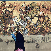 'Attitude at Altitude' Football in Potosi, Bolivia'..An early evening scene in Potosi, Bolivia as a women walks past a mural depicting the history of the town. Potosi, Bolivia, 12th May 2010. Photo Tim Clayton....'Attitude at Altitude' Football in Potosi, Bolivia'..The Calvario players greet the final whistle with joyous celebration, high fives and bear hugs the players are sprayed with local Potosina beer after a monumental 3-1 victory over arch rivals Galpes S.C. in the Liga Deportiva San Cristobal. The Cup Final, high in the hills over Potosi. Bolivia, is a scene familiar to many small local football leagues around the world, only this time the game isn't played on grass but a rock hard earth pitch amongst gravel and boulders and white lines that are as straight as a witches nose, The hard surface resembles the earth from Cerro Rico the huge mountain that overlooks the town. .. Sitting at 4,090M (13,420 Feet) above sea level the small mining community of Potosi, Bolivia is one of the highest cities in the world by elevation and sits 'sky high' in the hills of the land locked nation. ..Overlooking the city is the infamous mountain, Cerro Rico (rich mountain), a mountain conceived to be made of silver ore. It was the major supplier of silver for the spanish empire and has been mined since 1546, according to records 45,000 tons of pure silver were mined from Cerro Rico between 1556 and 1783, 9000 tons of which went to the Spanish Monarchy. The mountain produced fabulous wealth and became one of the largest and wealthiest cities in Latin America. The Extraordinary riches of Potosi were featured in Maguel de Cervantes famous novel 'Don Quixote'. One theory holds that the mint mark of Potosi, the letters PTSI superimposed on one another is the origin of the dollar sign...Today mainly zinc, lead, tin and small quantities of silver are extracted from the mine by over 100 co operatives and private mining companies who still mine the mountain in poor working conditions, ch