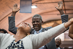 27 October 2019, Addis Ababa, Ethiopia: Rev. Abeya Sirika joins congregants in raising their hands in prayer during Sunday service at the Finfinne Oromo Mekane Yesus Congregation of the Ethiopian Evangelical Church Mekane Yesus. In a context where congregations did not use to be allowed to hold their services in any language but Amharic, the congregation today is one of some 60 Oromo speaking Mekane Yesus congregations in Addis Ababa. The service takes place on the first Sunday following political turmoil in the country, claiming dozens of lives.