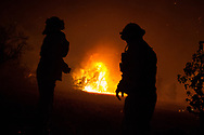 Firefighters cover their faces from smoke as residential buildings catch fire during the Woolsey Fire in Malibu, California, Friday, November 9, 2018. Over 295,000 people were evacuated during the fire.