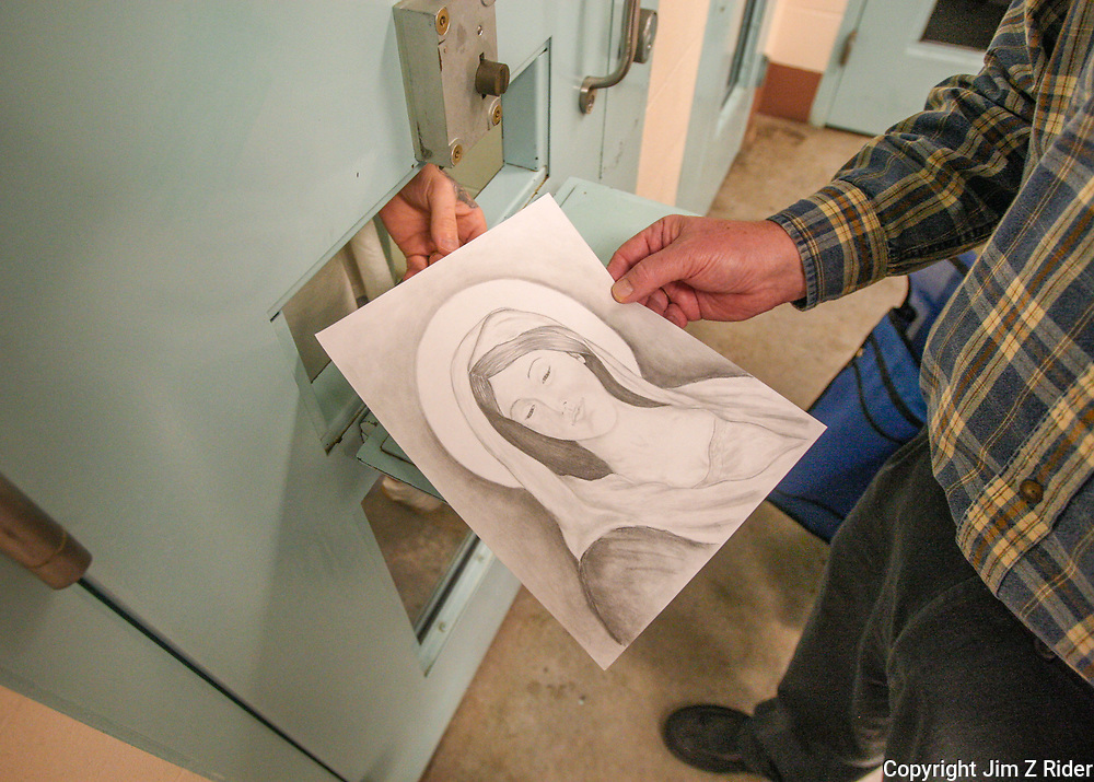 A prisoner shows Chaplain Coyle a drawing of the Virgin Mary created in his jail cell.