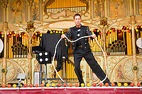magician doing magic tricks on stage at a country fair. with a pipe organ in the background