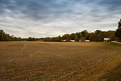A bare grain field provides a stark contrast but yet a scenic view to the farmstead and colorful fall trees behind it on an overcast day in Indiana