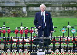 © Licensed to London News Pictures. 06/11/2012. Westminster, UK A man looks at the crosses already planted in the field. Soldiers prepare the Field of remembrance at Westminster Abbey today 6th November 2012 prior to it's opening on Thursday 8th November 2012 . The Field of Remembrance at Westminster Abbey pays tribute to all the brave Service men and women who have served in our Armed Forces since World War I. Photo credit : Stephen Simpson/LNP