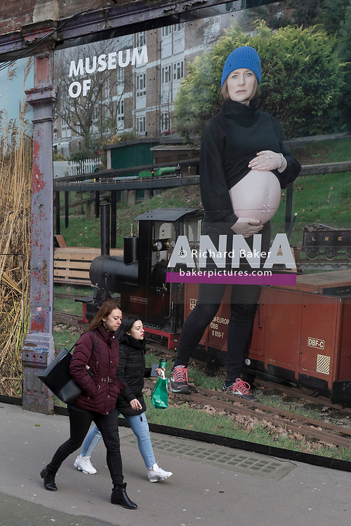A young lady walks past a large billboard, part of a series of portraits by photographer Lucy Alex Mac, that show pregnant women at West Smithfield, in the former Smithfield meat market that is awaiting future redevelopment, on 20th November 2019, at Smithfield in the City of London, England. As part of the Museum of London's plans to move into Smithfield's General Market Building, this photography show celebrates pregnant residents of Waltham Forest. The cost of the move is estimated to be in the region of £70 million and, if funding can be achieved, would be complete by 2021. There has been a market on this location since the Bartholomew Fair was established in 1133 by Augustinian friars.