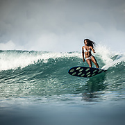 Nique Miller surfing at her home spot in Waikiki, Honolulu, Hawaii.