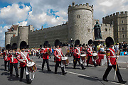 The Old Guard from the 1st Battalion Grenadier Guards, led by the Grenadier Guards Corps of Drums, leaves Windsor Castle following the Changing of the Guard ceremony on 29th July 2021 in Windsor, United Kingdom. The ceremony, which is also known as Guard Mounting, was reinstated on 22nd July for the first time since the beginning of the Covid-19 pandemic in March 2020.