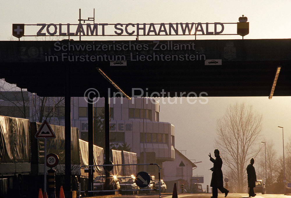 A customs officer holds up a hand to traffic passing through the national border between Liechtenstein and Austria, what the Austrians call a Zoll or Zollamt at Schaanwald, the north-eastern line near the Austrian town of Feldkirch, on 8th February 1990, in Schaanwald, Austria.