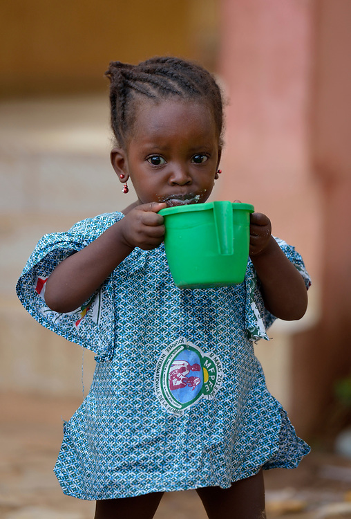 Two-year old Ayarina Maiga holds a cup of porridge in a camp in Mopti, Mali, for families displaced by fighting in the north of the country. Islamist rebels seized control of Maiga's home town of Gossi and other areas of the north in 2012, but were chased out in early 2013 by French troops. Many displaced and refugee families have yet to return, preferring to wait for better security and improved economic conditions in the north.
