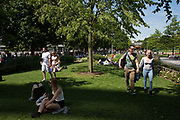 People gather on the grass in the summer sunshine at Jubillee Gardens on the South Bank in London, UK. The South Bank is a significant arts and entertainment district, and home to an endless list of activities for Londoners, visitors and tourists alike.