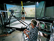 t the University of Utah in Salt Lake City, computer scientist John M. Hollerbach puts a lab staff member on the SARCOS Treadport, a device that mimics the tug and pull of acceleration. Walking on a treadmill, the staffer is surrounded by a projected simulation of a Western mountainside. On a real hill, hikers must struggle with their own inertia to surmount the slope, a sensation no ordinary treadmill can provide. The Treadport uses force-feedback to push or pull at the user, uncannily evoking the sensation of climbing, a new dimension of realism for this type of simulation. From the book Robo sapiens: Evolution of a New Species, page 137 top.