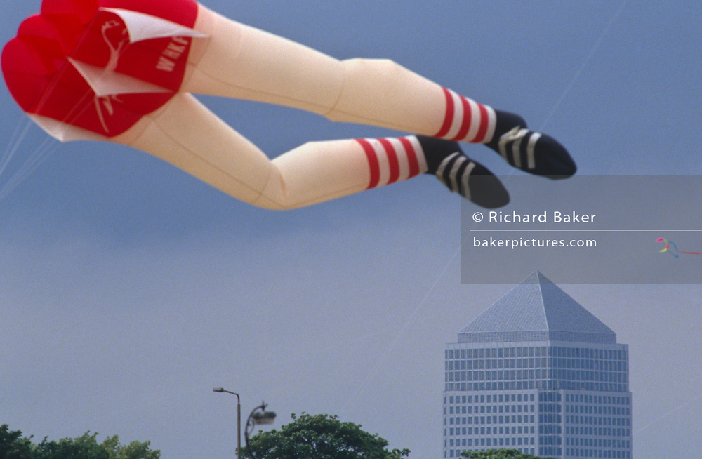 A compressed perspective image from the use of a long lens, with a kite in the shape of a pair of legs floating over the Canary Wharf office tower in 1991, in Blackheath, London, England.