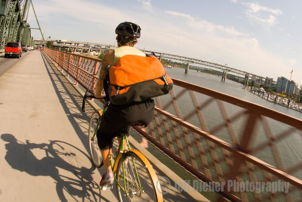 A young woman bike commuting across the Hawthorne Bridge in Portland, Oregon.
