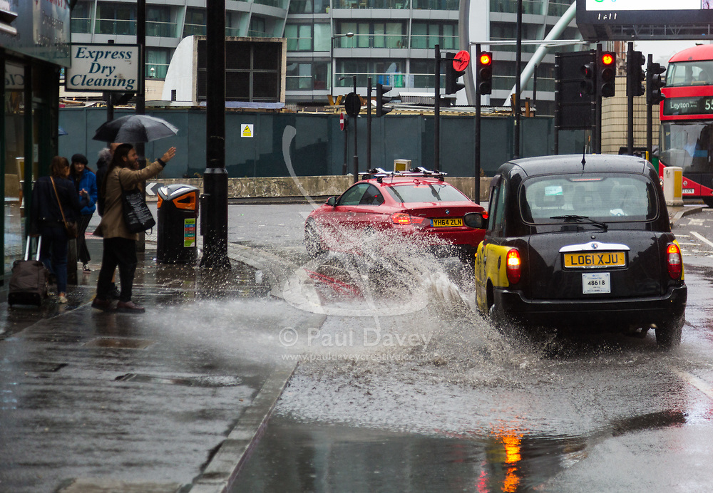 Constant rain on Bank Holiday Sunday leaves large puddles at Old Street Roundabout, with this taxi splashing water onto the pavement, causing pedestrians to gesture angrily. London, August 26 2018.
