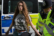 A young woman protester is arrested and searched by Met police officers at Oxford Circus on day 4 of protests by climate change environmental activists with pressure group Extinction Rebellion, on18th April 2019, in London, England.