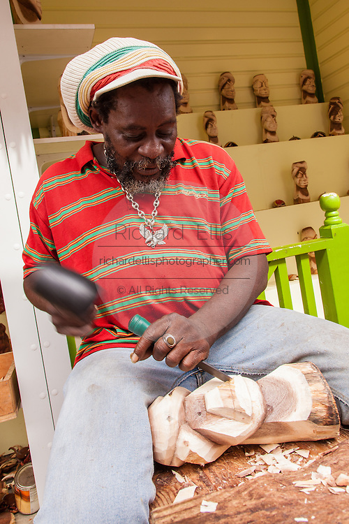 A wood carver works at the Straw Market in Nassau , Bahamas.