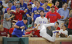 May 25, 2018 - Arlington, TX, USA - Texas Rangers third baseman Isiah Kiner-Falefa (9) chases a fly ball hit by Kansas City Royals third baseman Mike Moustakas (8) into the stands and makes the catch in the seventh inning as the Kansas City Royals play the Texas Rangers at Globe Life Park in Arlington, Texas, Friday, May 25, 2018. (Credit Image: © Rodger Mallison/TNS via ZUMA Wire)