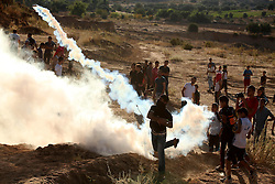 September 30, 2016 - Bureij, Gaza Strip, Palestinian Territory - A Palestinian protester throws back a tear gas canister fired by Israeli security forces during clashes near the border between Israel and Central Gaza Strip east of Bureij on Sep. 30, 2016  (Credit Image: © Ashraf Amra/APA Images via ZUMA Wire)