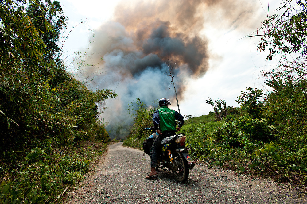 A motorcycle driver waits as a controlled fire burns on both sides of the one-lane road that connects the Naga Hills to the busy Chindwin River watershed. The ancient slash-and-burn method is still the most common form of cultivation in the jungles of northeast Myanmar.