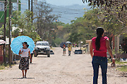 A woman carrying a blue umbrella walks down a street in the town of San Esteban, Honduras on Wednesday April 24, 2013.
