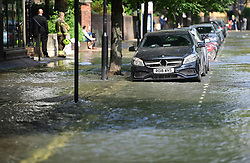 © Licensed to London News Pictures. 24/06/2021. London, UK. A river of water surrounds cars in St John's Wood, North London, where a burst pipe has has cause flooding across a number of streets in the area. Photo credit: Ben Cawthra/LNP