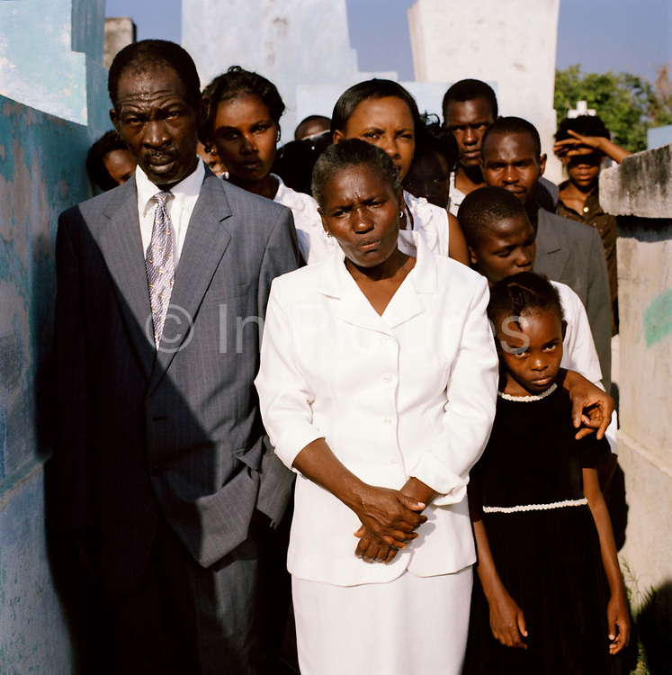 "Marie Ange St Laurent, (wearing white)  and her family, at the funeral of  Ronald St Laurent. ""Ronald was thirty-one years old when he died. His home fell down on top on him during the earthquake We were all inside but Ronald did not have time to get out.  We must thank God for the opportunity at least, to bury him properly. I feel sorry for the thousands of families who do not have this chance, many cannot find their loved ones. It will be hard for them to move on, it's double the problem.  At least we can visit and put flowers on the grave.  After the quake, there were bodies everywhere many were burnt where they lay or carted off in huge trucks to mass graves."""