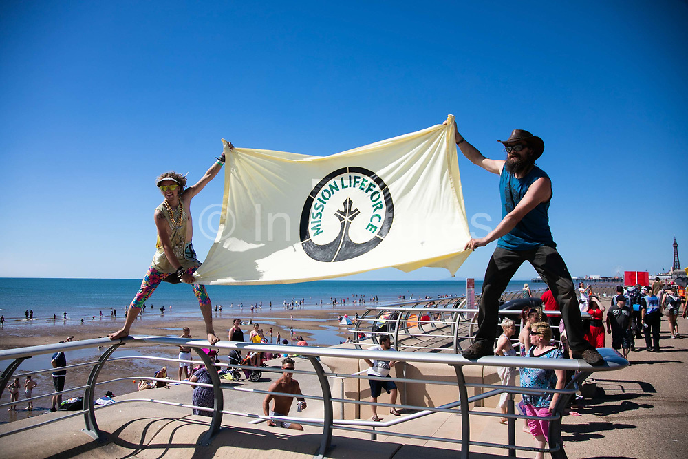Anti-fracking campaigners march along Blackpool sea front as part of the Block Around the Cloack event in Lancashire, United Kingdom, June 29th 2018.  Block Around the Clock - a fourty eight hours of event with work shops, yoga, sleeping and anti-fracking campaigning in front of the gates to Cuadrillas fracking site in Lancashire. The event was organised by anti-fracking campaigners in spite of an injunction granted to Cuadrilla to prevent protest against the impending shale gas exploitation. The Cuadrilla site in Lancashire in a highly contested site, almost ready to drill for gas.
