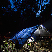 A researcher works late into the night in camp, Gunung Bondang Expedition, Central Kalimantan, Borneo, Indonesia. Run by the Heart of Borneo Rainforest Foundation.