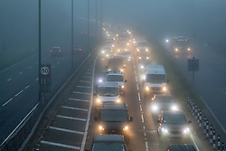 © Licensed to London News Pictures. 07/12/2020. London, UK. Traffic builds up in dense fog as commuters head into London on the A3 Kingston Bypass, South West London as the Met Office issue a yellow weather warning for freezing fog with disruption to transport for the South East of England this morning. The Government is expected to rolling out the new Pfizer/BioNTech's coronavirus vaccine tomorrow with reports it has already arrived in the UK for distribution to hospitals around the country. Photo credit: Alex Lentati/LNP