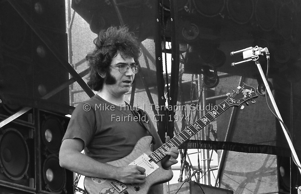 Jerry Garcia playing Guitar, and intently looking at something in the crowd. The Grateful Dead at Dillon Stadium in Hartford CT on 31 July 1974. Close in sidelong shot. Photo by Michael Thut, Fairfield CT.