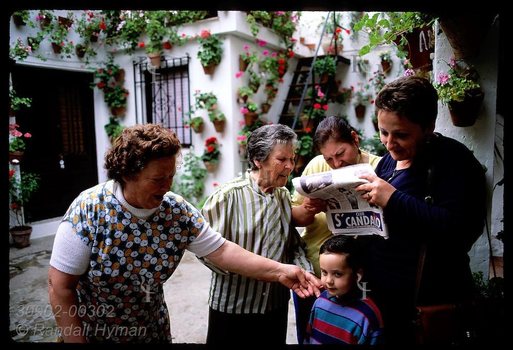 Courtyard women read paper over boy's head & gossip about Festivl de los Patios winners; Cordoba. Spain