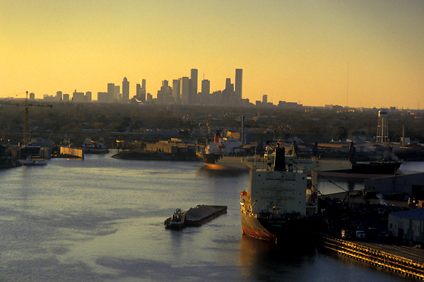 Shipping vessels in the ship channel at the Port of Houston with the downtown Houston skyline on the horizon at sunrise.
