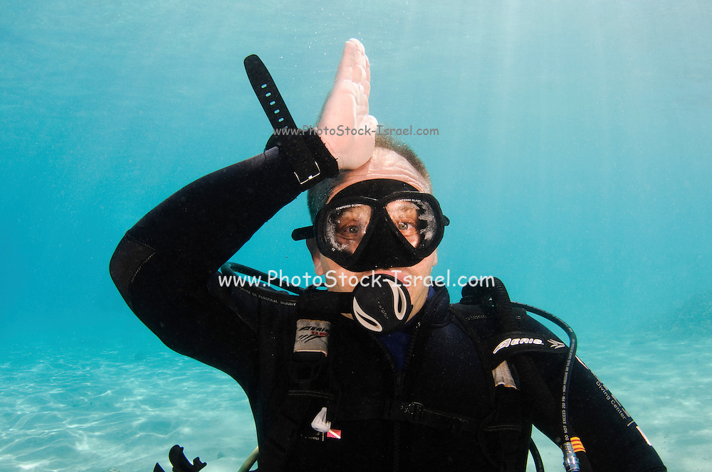 Shark alert or beware of approaching shark. Underwater Hand signs scuba diver demonstrates the sign language for divers.