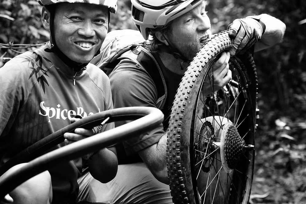 Andrew Whiteford and Win Jalawin fix a flat tire on the single track in the jungle near Ban Sop Gai, Thailand.