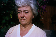 A middle'-aged while in her back garden during the 1980s. It is a close-up detail of the lady's face that shows the lines and wrinkles of a long life, her silver hair swept in a side parting. She sits in summer sunshine in her back garden with a worried look on her face.